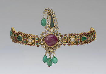 A turban ornament with a large cabochon ruby in its centre encircled by diamonds, with cabochon emeralds hanging above and below the ornament. Attached to either side of the turban ornament are bands of alternating gold tablets inlaid with emeralds, rubie