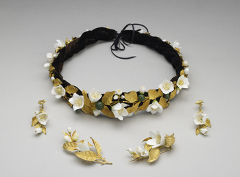 <p>Headdress in the form of a wreath of orange blossoms with gold leaves, white porcelain flowers and green enamelled oranges. Black plaited velvet band, and silk ribbon.</p>