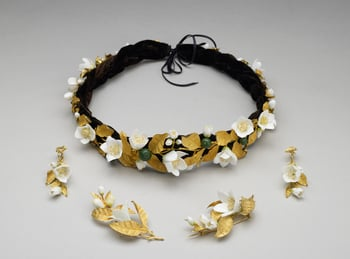 Headdress in the form of a wreath of orange blossoms with gold leaves, white porcelain flowers and green enamelled oranges. Black plaited velvet band, and silk ribbon.