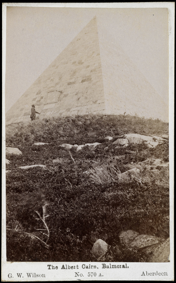 Photograph of Prince Albert's memorial cairn constructed on top of Craig Lurachain on the Balmoral Estate. Moorland dominates the foreground with the cairn, of triangular construction, standing in the background. On the left stands a ghillie who inspects