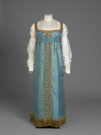 Dress, full length, sleeveless; blue silk trimmed round bodice and down centre skirt with scalloped gold lace with red highlights; skirt edged with gold fringe: separate front opening bodice, drawstring high-waisted flared/gathered skirt