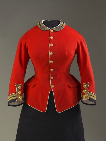 Military jacket; red wool, high neck, 8 evenly spaced brass buttons centre front, flared back skirt w 8 buttons, 3 cuff buttons; black twill, metal lace & white wool piping on cuffs & collar; cream silk lining