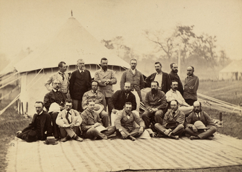 Photograph of Albert Edward, Prince of Wales (1841-1910), later King Edward VII, during his 1875-6 tour of India. The Prince is photographed with a group of gentlemen who accompanied the Prince on his tour. There is a tent behind them.