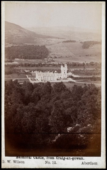 Photograph of the new Balmoral Castle in Aberdeenshire taken from a high vantage point with woodland in the foreground and hills in the background