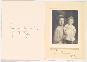 Photograph of Princess Elizabeth (b. 1926), seated, facing the viewer with the infant Prince Charles (b. 1948), who is standing up, supported by his mother. This image, taken during Prince Charles's first sitting with Adams on 26 October 1949, was chosen