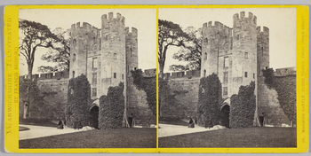 Stereoscopic image of Warwick Castle, with the Clock Tower seen from the Inner Court. A woman, and two men stand in front of the archway, probably the photographer's wife and two sons. 