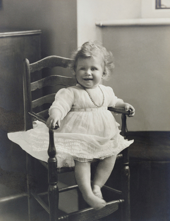 Photograph showing full length informal portrait of HRH Princess Elizabeth of York aged approximately one year, seated in a wooden chair and facing three-quarters right. Mounted photograph