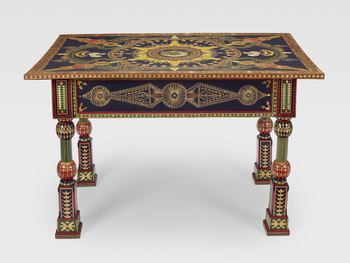 A Russian wooden table painted in dark blue, red and green and inlaid with straw in geometric patterns. The centre painted with the conjoint arms of the Duke and Duchess of Edinburgh.