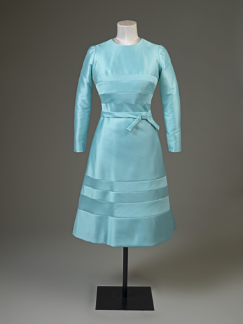 Day dress, blue wool/silk mix tailored bodice, round neck, long sleeves with wrist zip, slightly flared knee-length skirt; dress embellished with inset bands of fabric reversed; narrow belt with bow at left side