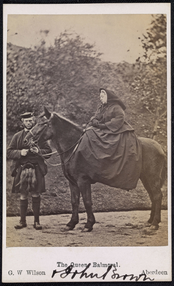 Photograph of Queen Victoria (1819-1901) seated on her pony 'Fyvie' which stands in left side profile. Holding the horse's reigns is John Brown (1827-83) who stands facing the viewer. As a tribute to her recently deceased husband, the Queen commissio