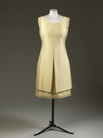 Dress, pale yellow [?] silk/wool mix, sleeveless, round-neck bodice, slightly flared knee-length skirt, attached overdress; embroidered at armholes and skirt hem w lattice of bugle beads & pearls