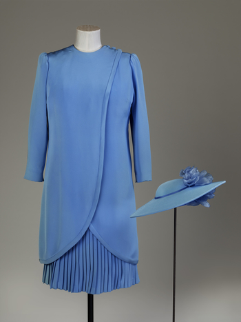 Dress, medium blue silk crepe, French pleated, knee length skirt attached to silk underbodice, attached to jacket with long sleeves, wrap-over front, fastening on left shoulder with threeself covered buttons, fronts taper towards back from waist