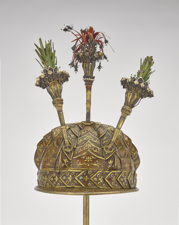 Semi-elliptical gilt-copper helmet or top of scale armour, ribbed with a small frontal peak and fortified with horny scales and surmounted by three porte-aigrettes; lined with green velvet. Each scale decorated with gold paint and the scales near the rim