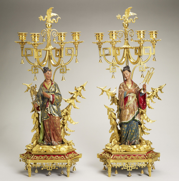 A set offour light candelabra, different in design but similar in composition: each holds a percussion instrument and stand on a rocky base strewn with plants and vegetation; behind are tress and a central bamboo shaft which are attached to th