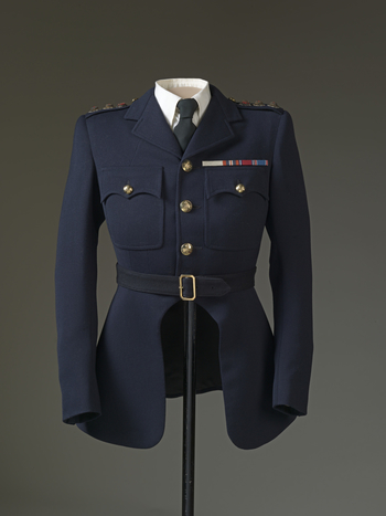 Grenadier Guards, No. 1 Dress; known as a 'Jumper'. Blue wool tailored jacket with three badges of the Grenadier Guards attached at epaulettes; four brass buttons centre front, one at each breast pocket and at each cuff; split skirt from waist.<br /><br /