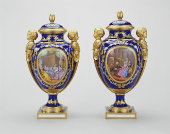 Decorated with a bleu nouveau ground and boy herm handles, in imitation of gilt bronze, the vases are known as vases des âges and are of the smallest - the third - size produced.   The vases would certainly have been destined for luxurious, neo-classic