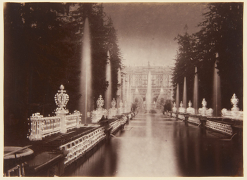 Photograph of the fountains in front of the Grand Palace at Peterhof, illuminated at night. In the foreground is a long pond, lined on either side by fountains, illuminations and trees. The Grand Palace can be seen in the distance behind the Grand Cascade