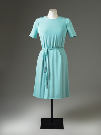 Dress, turquoise silk, loose bodice, round neck short sleeves, gathered into skirt at front, skirt with two box pleats front; lined white silk; attached belt of three silk tubes with strands of blue beads at ends
