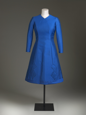 Day dress, blue wool/silk mix, fitted bodice with V neck at front, long sleeves slit at wrist, knee length slightly flared skirt, two side seams end in diamond shaped same fabric insets at hem