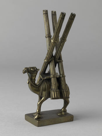 A brass statuette of a camel, saddled, with four long bundles of fasces which cross alternately. The figure modelled and cast using the lost-wax process used in India to create images of Hindu deities.