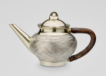 A Russian silverand parcel gilt teapot with detachable cover. The pot with an angular brown leather covered handleand astraight spout. The body castand chased with awoven reed pattern.   Lid struck with city mark of St