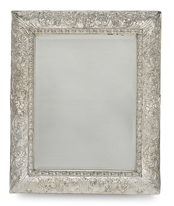 A rectangular silver mirror with embossed decoration, the inner part of the frame chased with leaf husks, the outer rounded area with foliate arabesques overlaid at the centre on either side with a bearded male mask.