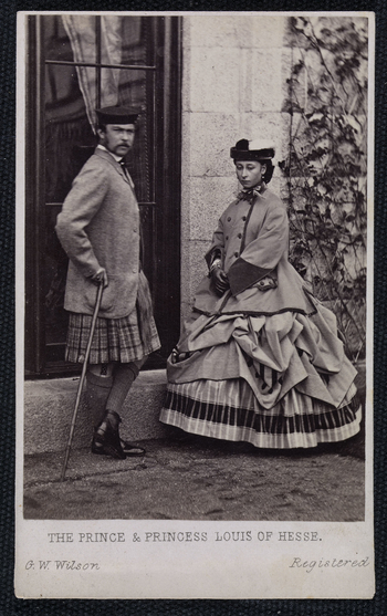 Photograph of Princess Louis of Hesse (1843-78), later the Grand Duchess of Hesse and by Rhine, standing outside a building at Balmoral. On her right stands Prince Louis of Hesse (1837-92), later the Grand Duke of Hesse and by Rhine who stands in fro