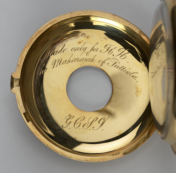 A gold half hunter watch decorated with enamel and set with diamonds. The outer case on the dial side is decorated with two concentric circles; the inner circle has the 12 hours represented in Roman numerals painted in white on blue enamel and the outer c