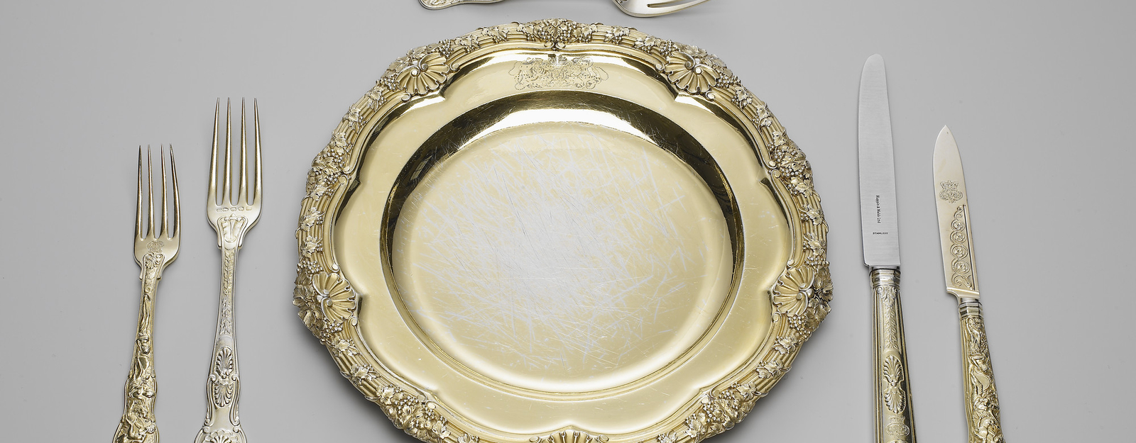 A set of silver-gilt plates; the reeded rim cast with fruiting vines and scallop shells. The plate is engraved with the Royal coat of arms, with supporters, mantling and coronet.