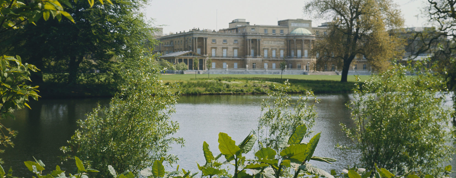 The rear facade of Buckingham Palace seen from the garden lake