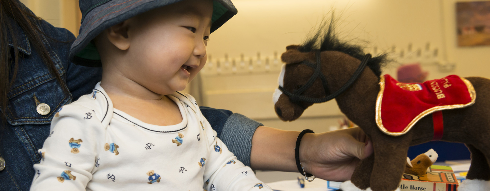 Baby with a cuddly toy horse