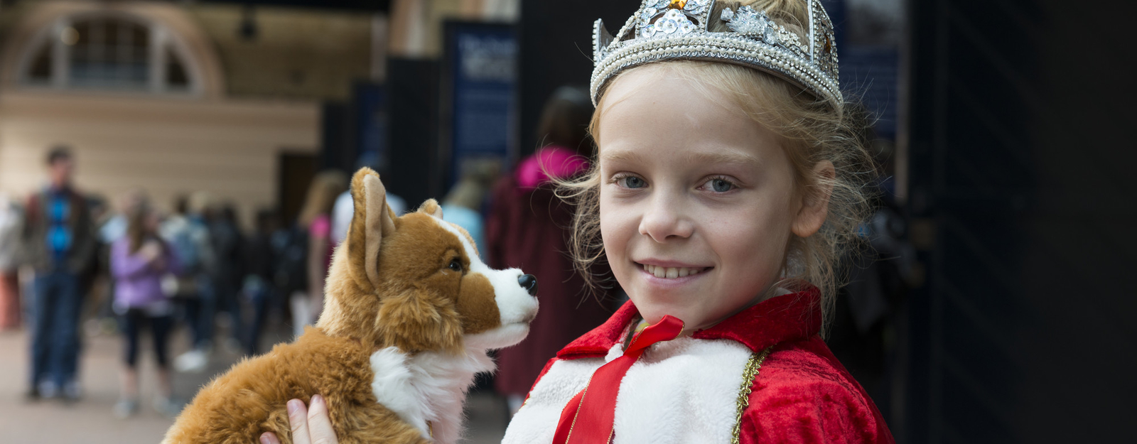 Girl dressed as a queen holding a toy Corgi