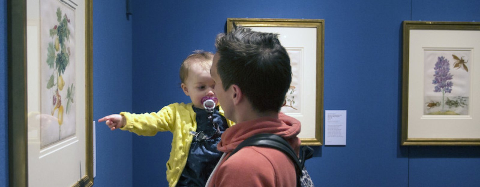 Man and a baby looking at a work of art