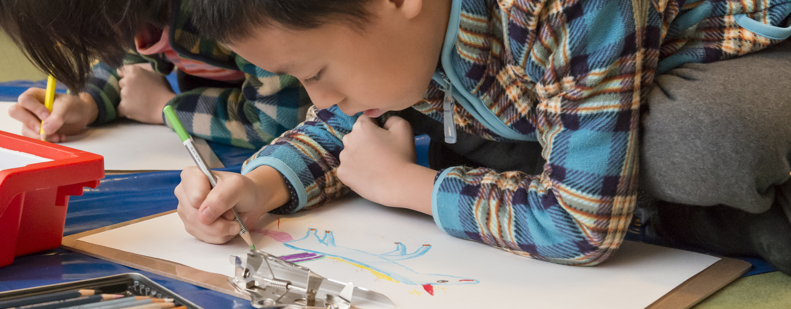 Child drawing with candles