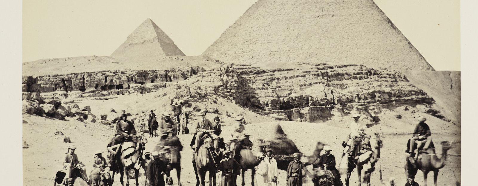 The Prince of Wales and his entourage on camels posing for camera in front of Pyramid of Cheops and Pyramid of Cephrenes, Giza, Cairo. The Prince is seated on the camel fifth from the left. The man in the white suit with a cigar, gazing up at the Prince,