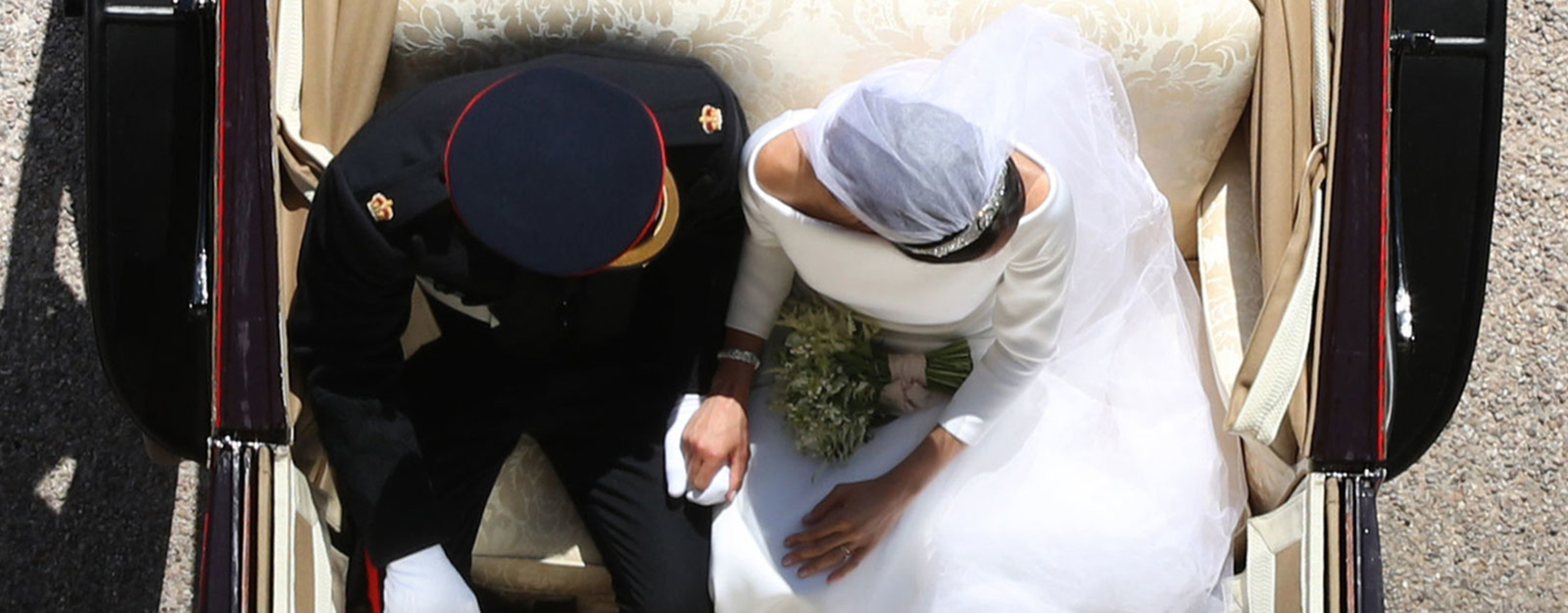 The Duke and Duchess of Sussex holding hands in the carriage following their wedding