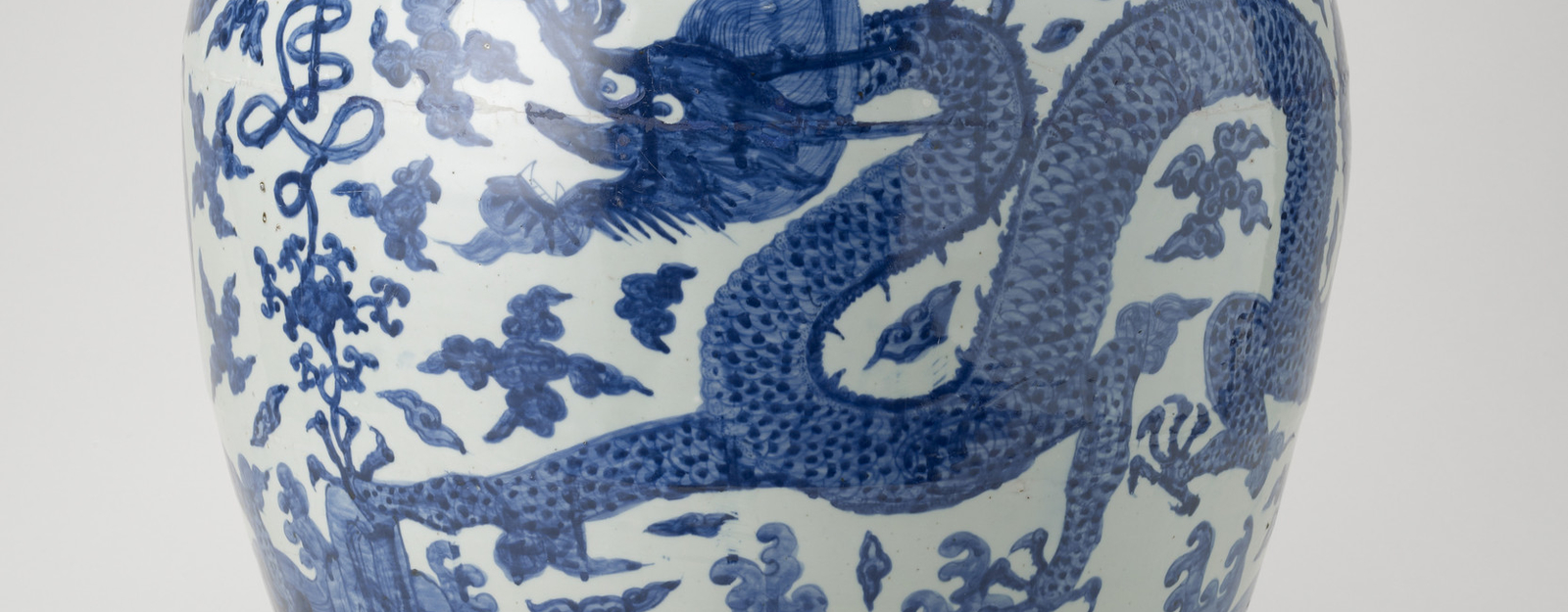 An ovoid-shaped Chinese Ming period porcelain jar painted in rich blue around the sides with two five-clawed dragons among clouds and with rocks and waves below. Round the shoulder a stylised shou (long life character) seems to grow out of the lotus