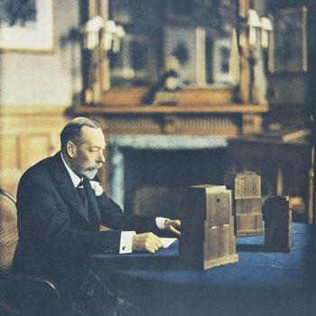 <p>Print from a Vivex photograph of King George V (1865-1936) recording his Christmas radio broadcast at Sandringham. He is sitting at a round table with his speech, the microphone and the recording equipment in front of him. This print was issued by