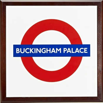 A square enamel plaque with the London Underground logo and inscribed BUCKINGHAM PALACE. Framed in wood.  The first use of a roundel design was at St. James's Park underground station in 1908. The font has since been slightly modernised but the basic fo