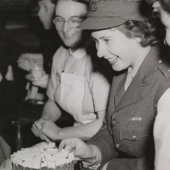 Photograph of Princess Elizabeth accepting a piece of cake at a tea party at the Royal College of Nursing