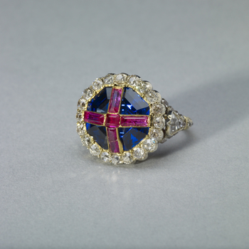 The ring comprises an octagonal step-cut sapphire, open-set in gold, overlaid with four oblong and one square rubies in gold strips forming a cross, within a border of twenty cushion-shaped brilliants in transparent silver collets. Brilliants decorate the