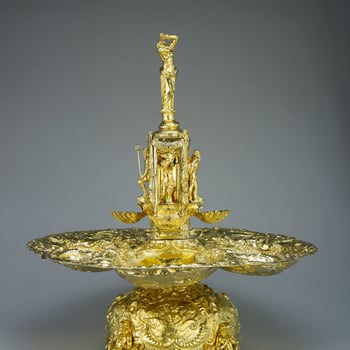 Silver-gilt Baroque fountain with four spreading basins, repousse and chased with marine scenes andfigures of Neptune, Amphitrite and infant tritons with sea-monsters, surmounted by a square column with figures of Neptune or nymphsin niches on