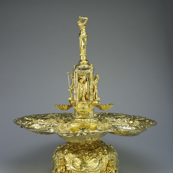 A Baroque silver-gilt fountain with four spreading basins, repousse and chased with marine scenes and figures of Neptune, Amphitrite and infant tritons with sea-monsters, surmounted by a square column with figures of Neptune or nymphs in ni