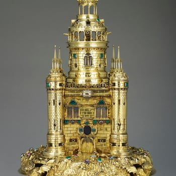 A silver-gilt table salt in the form of a tower with cylindrical corner turrets and a tall central turret with an open gallery and domed roof above, resting on a chased mound supported by dragons on ball feet, the salt is encrusted with jewels. The body o