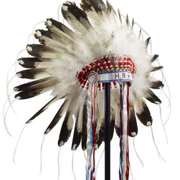 A First Nations feather headdress or warbonnet in Plains style, fitted with eagle (?) feathers threaded with white horsehair (?) at the tips and with blue, red, purpleand white silk ribbons hanging from each side,and a blueand whit