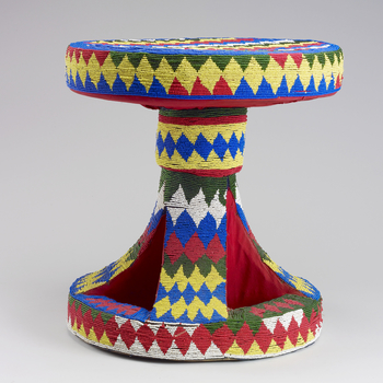 A stool with a circular seat and base covered all over with red, yellow, white and blue glass beadwork in a zig-zag pattern. The size and decoration of Cameroon's ceremonial stools symbolise the status of the individual to whom the stool belongs. The empt