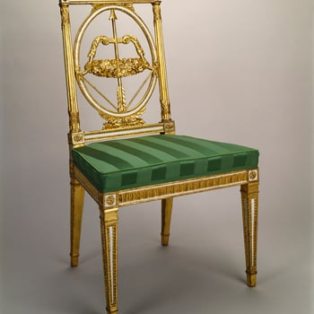 A giltwood and white painted side chair, the rectangular back with an oval-framed bow and arrow splat carved with a wreath of flowers; rectangular uprights bound with carved ribbon. Some areas painted white.Square reeded legs. Upholstered in green s
