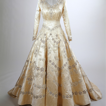 Wedding gown of the then Princess Elizabeth; rich ivory duchesse satin contrasting with the white seed pearls, imported from America, silver thread, sparkling crystal and transparent appliqué tulle embroidery. Attached at the shoulders was a magnificent