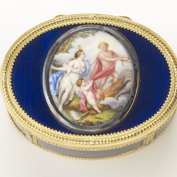Oval gold and enamel hinged box. Cover with an oval painted enamel plaque painted with a scene of Mars and Venus, straight sides divided into panels of blue guilloché enamel divided by chased gold borders. The tale of the god of war, Mars, being tamed by