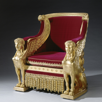 Pair of council chairs of carved and gilded pine and beechwood, covered in red velvet with gold trimmings and fitted with a cushion and valance. Backs shaped like Roman chariots, are solid to the ground and elaborately carved, as is the whole. Padded velv
